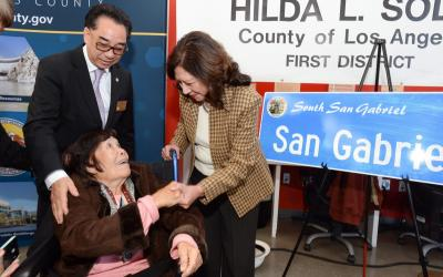 Image of elderly woman in a wheel chair shaking hands with another woman