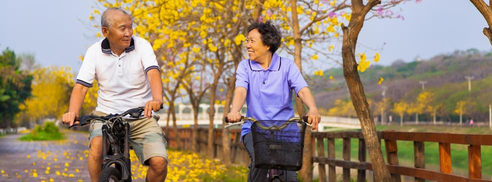Image of a male and a female riding bikes along a road