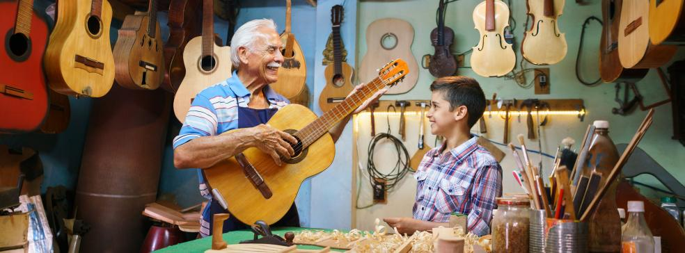 senior man teaching grandson the guitar