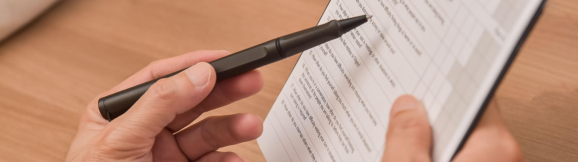 Zoomed in Image of a hand holding a pen and a clipboard