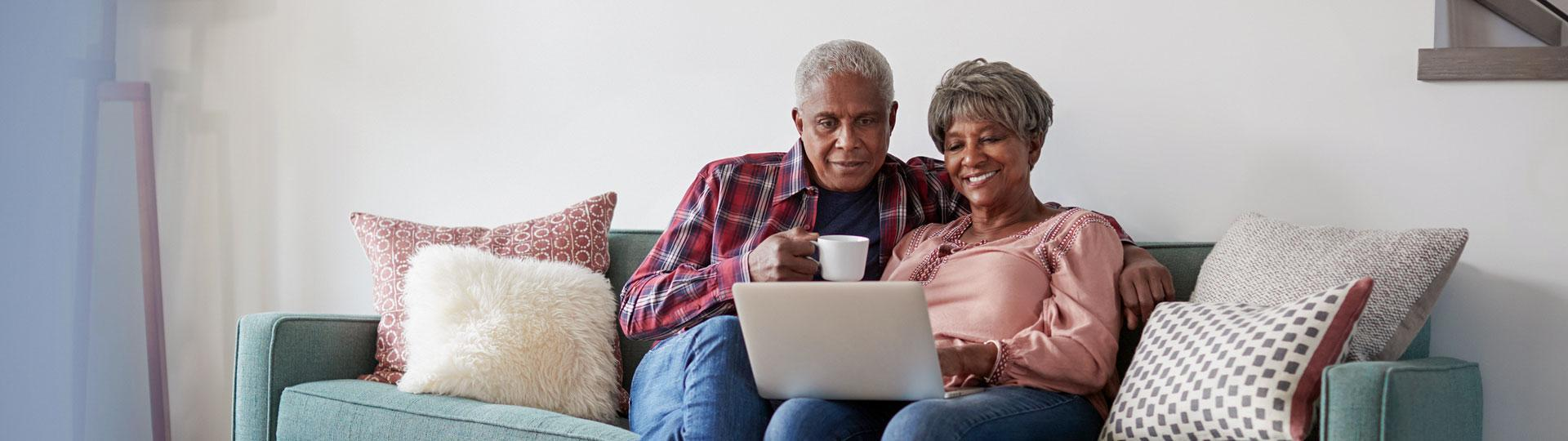 Image of a senior couple sitting on the couch looking at a laptop